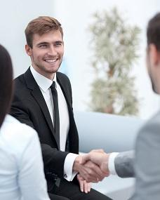 Young man in suit smiling and shaking hands